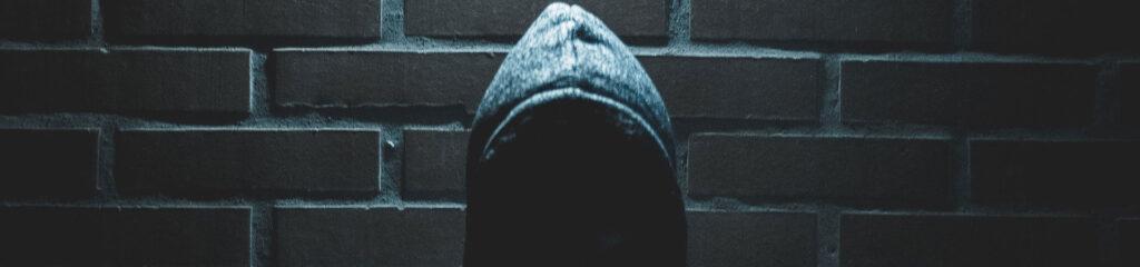 homme portant un sweat à capuche dans l'ombre