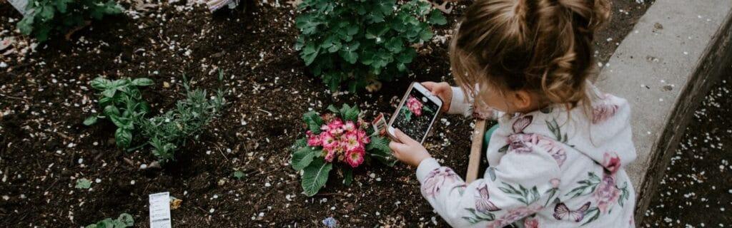 une enfant prenant fleurs en photo