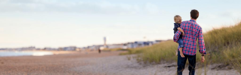 un père avec son enfant à la plage